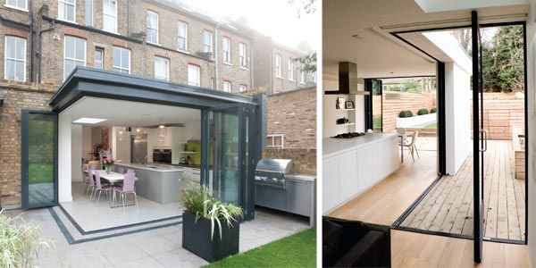 Folding doors wrap around the corner of this extended kitchen designed by Architect Your Home; This project by William Tozer Architecture & Design accommodates an open-plan kitchen, living and dining space to the rear of a Victorian house
