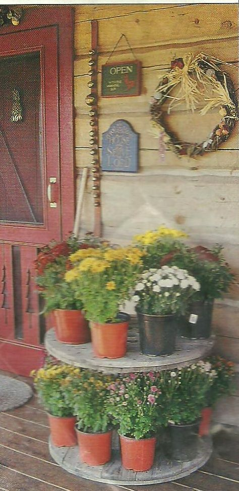 So simple, but so beautiful.  Country Woman magazine, 2004.  Using an old electric cable spool for displaying fall flowers.