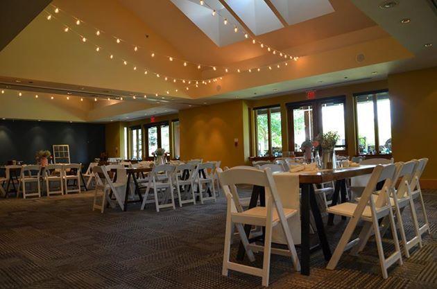 Indoor vintage farmhouse. Harvest tables. Edison light bulbs. White folding chairs.