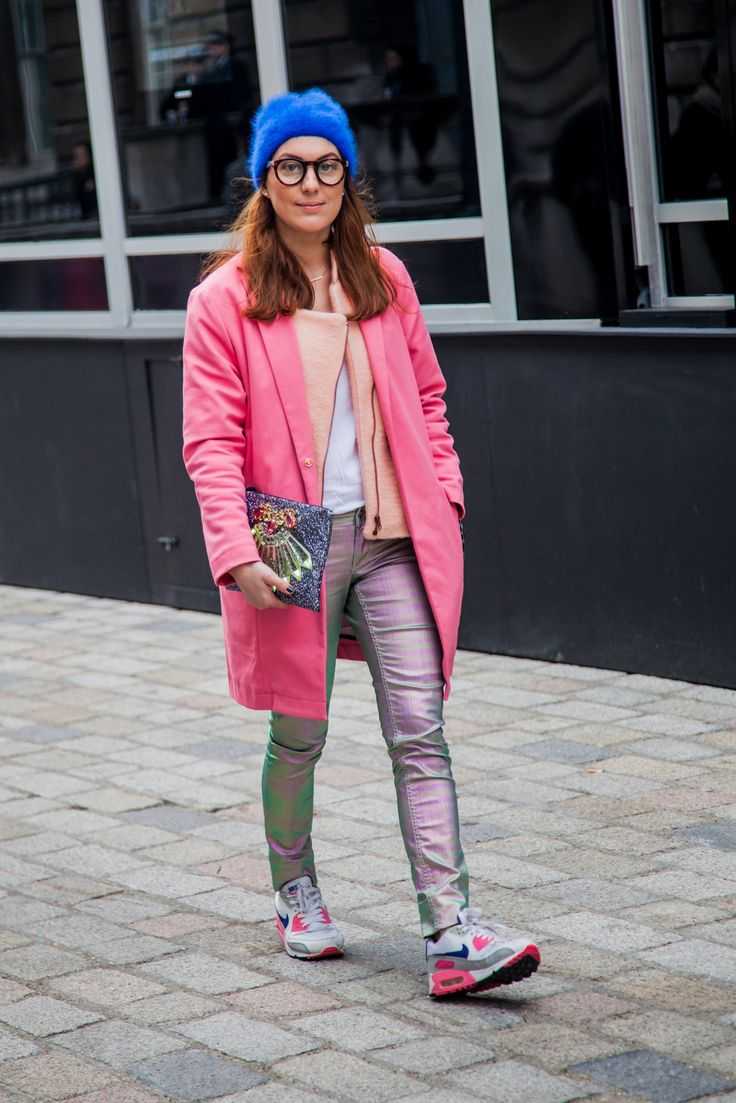 A fashionista mixes her pink coat with kicks and a cobalt hat at London Fashion Week.