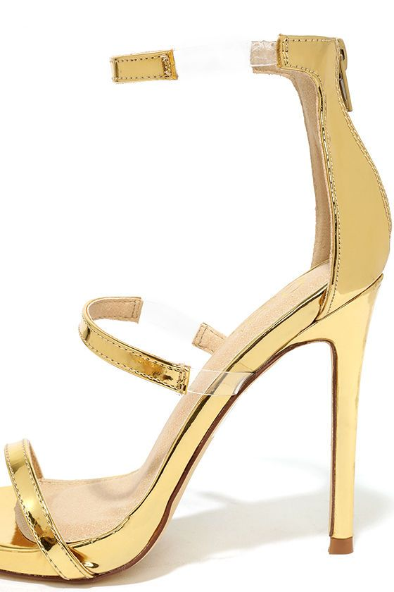"The Making Magic Gold High Heel Sandals create a sexy illusion that will have all your admirers mystified! Shiny, mirrored vegan leather forms these single sole heels with lucite accents along the strappy peep-toe upper. 3"" heel zipper."