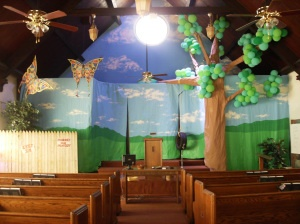 butterflies, clouds hanging from ceiling as well as hula hoops with ribbon/streamers; tree on stage