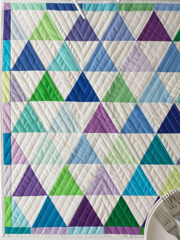 Work with 60 degree triangles in this quick, easy, and fun pattern. Alternate colored triangles and white triangles to create a rhythmic pattern. Finished Size: 21