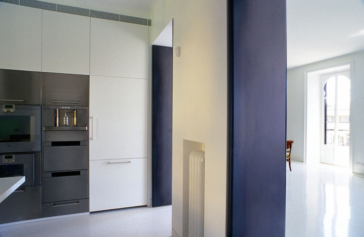 modern white glossy lacquered kitchen and large iron doors, for a bright apartment in Milan.
