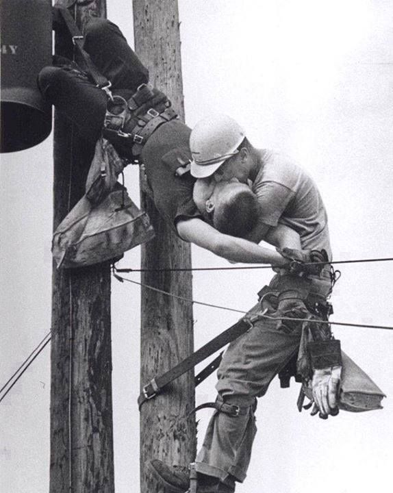 "This 1967 award-winning photo entitled ""Kiss of Life"" shows two power linemen, Randall Champion & J. D. Thompson, at the top of a utility pole. They had been performing routine maintenance when Champion brushed one of the high voltage lines at the very top. Over 4000 volts entered Champion's body & instantly stopped his heart. His safety harness prevented a fall & Thompson, who had been ascending below him, quickly reached him & performed mouth-to-mouth resuscitation."