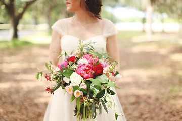 this florida bride chose an organic and loose unstructured bridal bouquet of coral charm peonies, red ranunculus, Vendala roses, hot pink ranunculus, light pink lisianthus, jasmine vine, lemon leaf, peach stock & seeded eucalyptus wrapped in cream muslin ribbon.