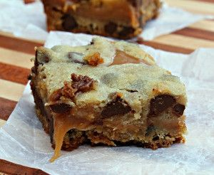Chocolate chip cookie bars are stuffed with a layer of melted caramel peanut butter sauce