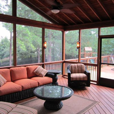 This screened porch epitomizes cozy outdoor living with exposed rafter ceilings and low-light wall sconces. With wide screen openings the view out to the yard is unobstructed and the flooring is carried through to the adjoining deck with a gorgeous diagonal pattern. With the addition of a ceiling fan, this Durham screened in porch is sure to be a comfortable living space any time of year.