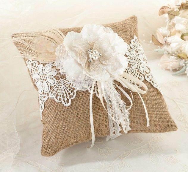 Toute la délicatesse de la dentelle sur ce coussin à alliances en toile de jute décoré d'une fleur et de plumes