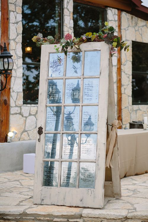 rustic and vintage inspired door with seating chart written on glass panes, photos by Caroline + Ben Photography | via junebugweddings.com