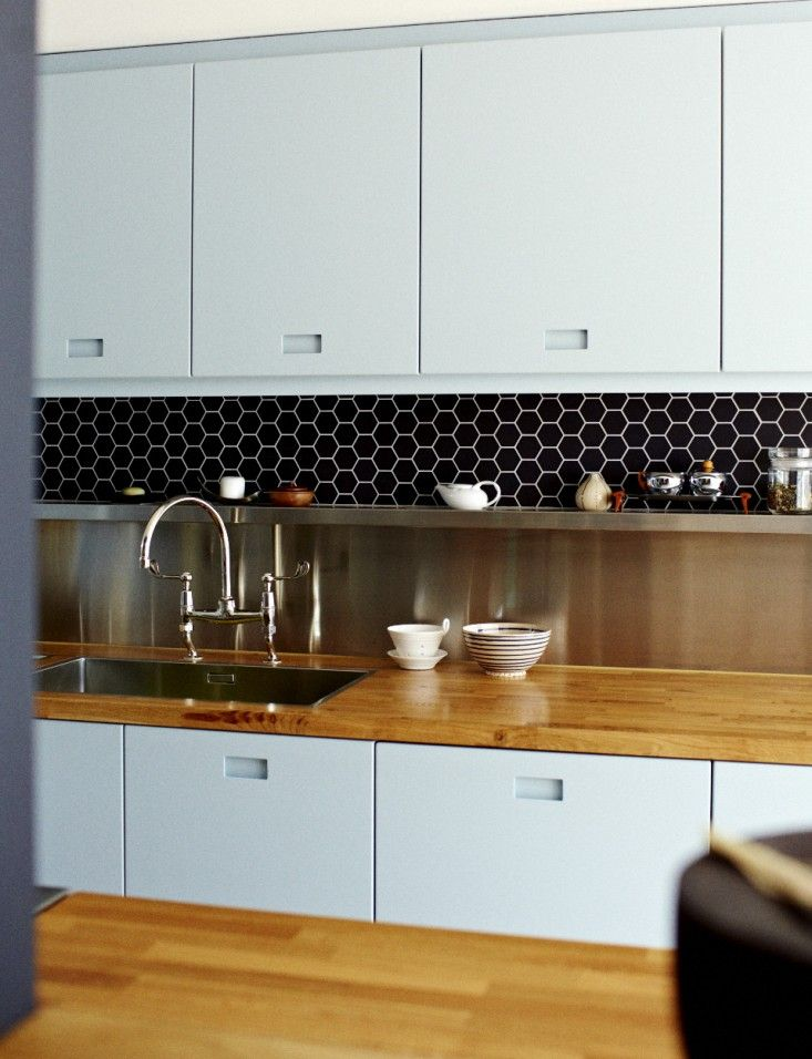 blue-grey kitchen cabinets+ routed out handles + solid wood countertop + stainless steel backsplash with shelf + black hexagonal tiles
