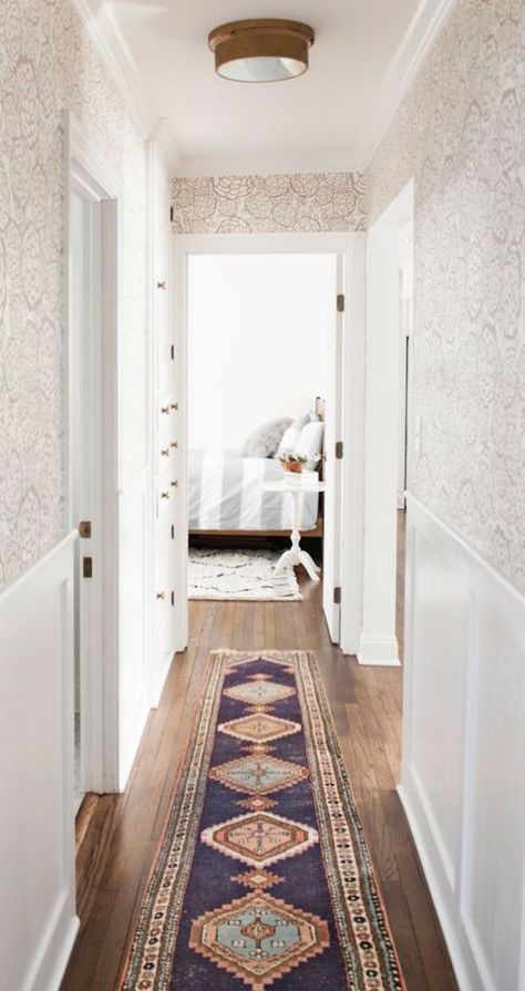 patterned wallpaper in the hallway with antique runner