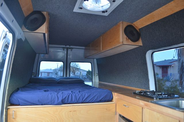 DIY Sprinter camper van interior, showing bed, cabinets and cooktop (photo: 3Up Adventures)