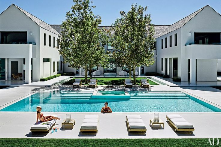 Von Furstenberg looks on as Miller takes a dip in the terrazzo-lined swimming pool; the lounge chairs are by Summit Furniture.