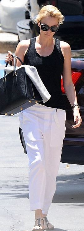Who made  Charlize Theron's sunglasses and black tote handbag?