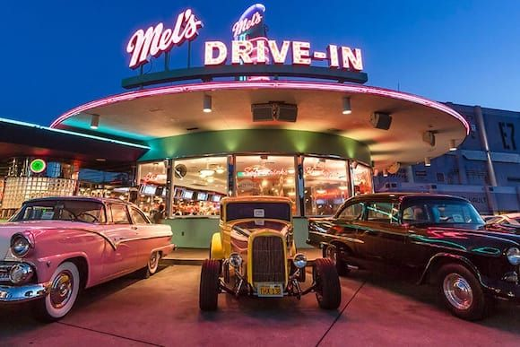 The exterior of Mel's Drive In in Universal Studios Orlando with neon signs illuminated at night and vintage cars parked out front.