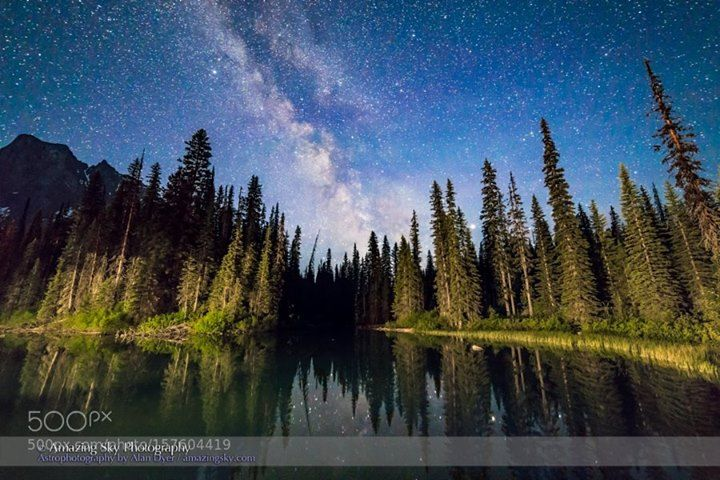 The Milky Way at Emerald Lake Yoho  The Milky Way over the side pond at Emerald Lake Yoho National Park BC. from the bridge to the Lodge. Lights from the Lodge illuminate the trees. Perpetual twilight near solstice (I shot this JUne 6 2016) lights the sky deep blue. Saturn is the bright object in haze shining through the trees at right. This is a stack of 8 x 25-second exposures for the foreground (mean combined to smooth noise) and one untracked exposure for the sky (to minimize trailing)…