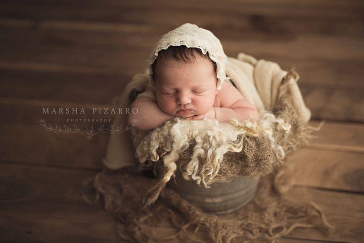 newborn baby girl in a vintage bucket of cream curls wearing a vintage cream…