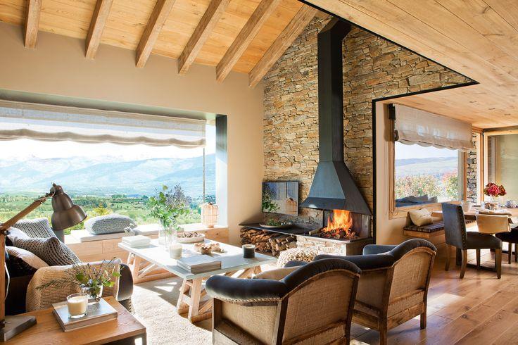 Salón rústico con vigas de madera, pared de piedra, chimenea y vistas al comedor