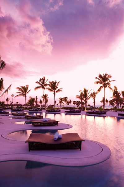 The sun sets over chic lounge chairs surrounding the expansive infinity pool at Secrets Maroma Beach!