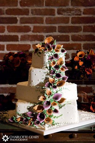 Wedding cake with orange and purple sugar calla lilies; I don't know if you'll like this, but I do! kn