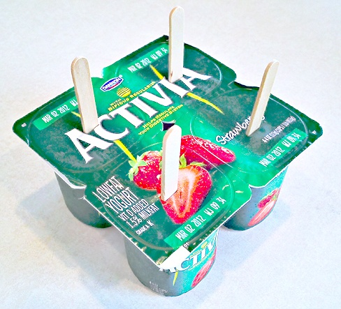 So last night at the grocery store I picked up this four-pack of strawberry yogurt singles, came home, poked in the four popsicle sticks and popped them in the freezer. (Annie used spoons, but the popsicle sticks worked great!)