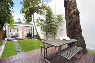 Decking around the shade tree is great solution for too large of a yard/grass space without pouring more concrete, easily removed or changed if needs change.  This would be option in B's backyard!
