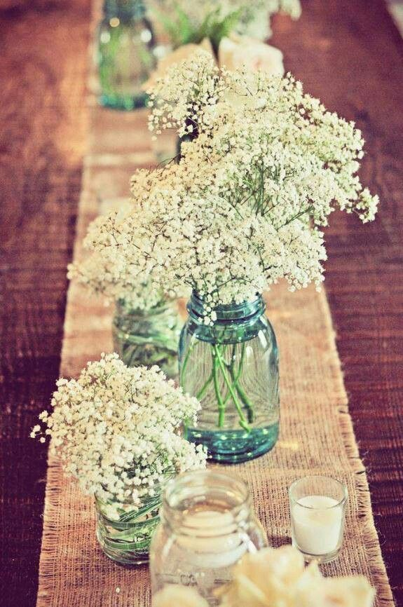 Baby's breath in mason jars on burlap runner as the centrepiece of a wedding dinner table.