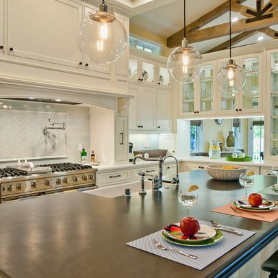 Bright White Kitchen Features Over Sized Dark Island And