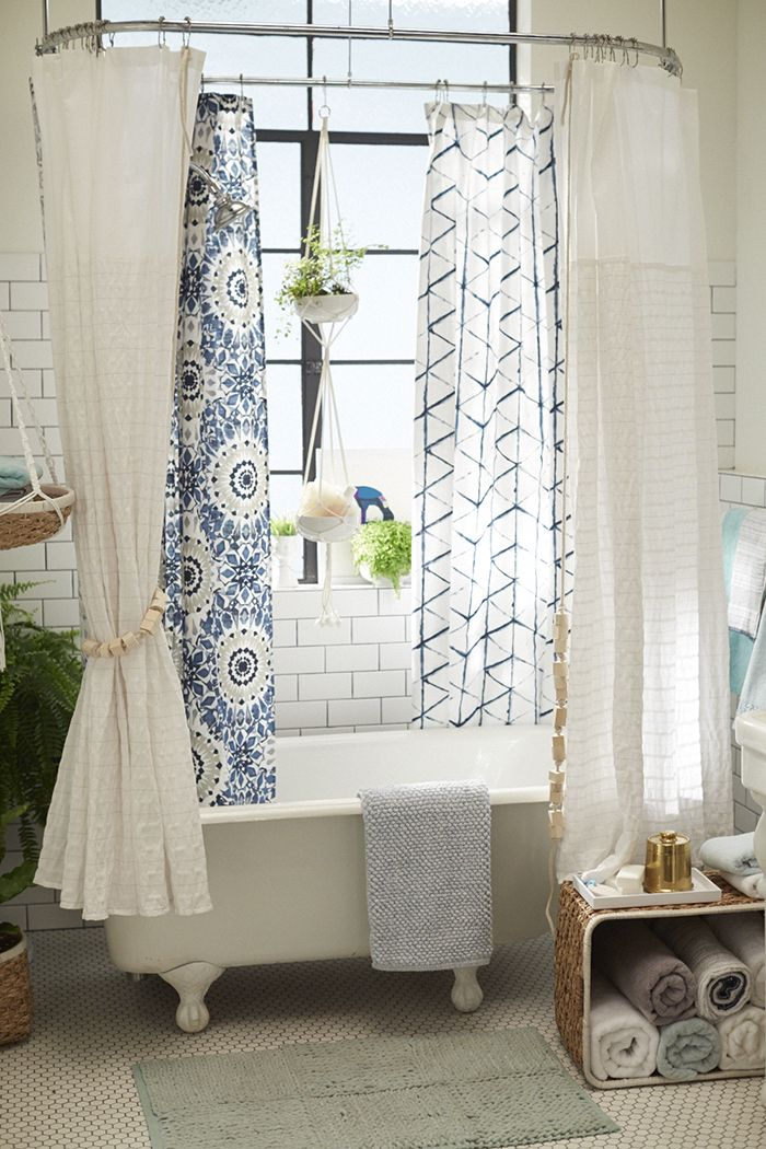 Multiple kinds of shower curtains plus macrame plant holders for storing shower supplies! Great ideas!!