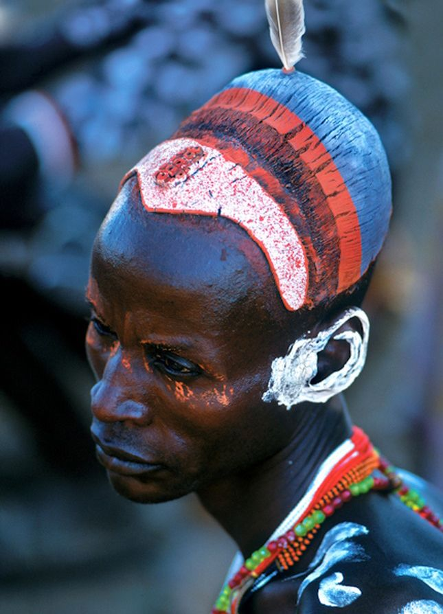 "Africa | ""The painted hair buns of Karo men symbolize their courage and bravery, and often indicate that they have killed a dangerous wild animal or enemy. The gray and white egret feather inserted into the hair bun adds an extra touch of beauty. Ethiopia"" 