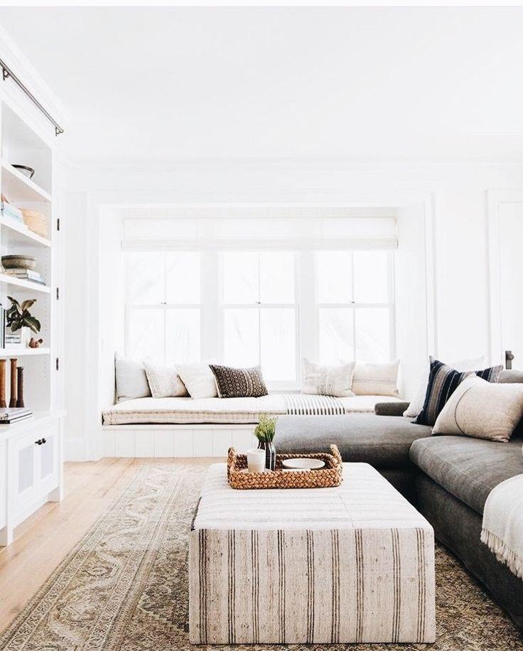 Sala bem iluminada com janela e seat window. Móveis com cores neutras.