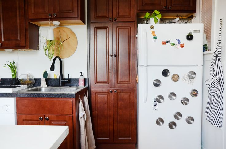 Magnetic storage containers on the fridge organize small household items like rubber bands and paper clips.