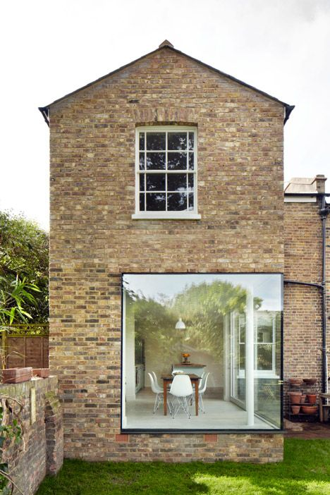 A large window wraps around one corner of this brickwork extension to a Victorian house in London by local office Cousins and Cousins