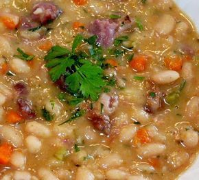 White Bean and Ham Soup:1 pound dry navy beans, soaked overnight 4 quarts water 1 pound leftover ham bone with meat attached 1 onion, finely diced 2 carrots, sliced 2 stalks celery, diced 2 bay leaves 1/4 teaspoon garlic powder 1/4 teaspoon ground black pepper 1/2 teaspoon paprika