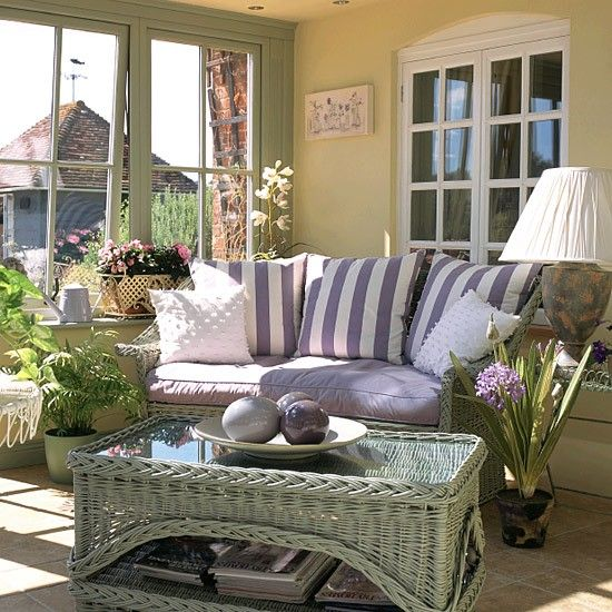 The conservatory of this Victorian house is painted in Teknos duck-egg, lavender and gardenia to complement the garden. Matching duck-egg wicker furniture has striped blue cushions for contrast. Windows are large to let in light and make the most of the garden beyond. Pale terracotta tiles hide underfloor heating.