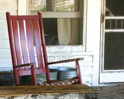 Red Rocking Chair On The Porch Of An Old Farmhouse Stock Photo