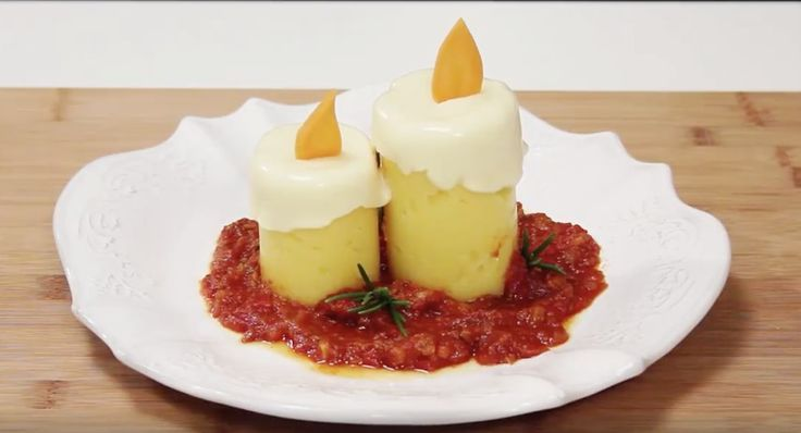 Una deliziosa polenta a forma di candele di Natale! Taglia un vecchio barattolo e versa in ogni metà della polenta. Con delle fette di formaggio fuso crea l'effetto della cera e con una carota la fiamma. L'effetto finale è un vero spettacolo!  Fonte Video: http://www.visualfood.org