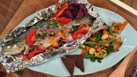 Forelle in Alufolie mit verschiedenem Gemüse und Pumpernickel auf einer Platte