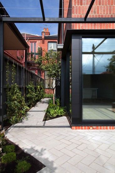 Recycled red brick (for exterior) with black glazing and simple black steel pergola.