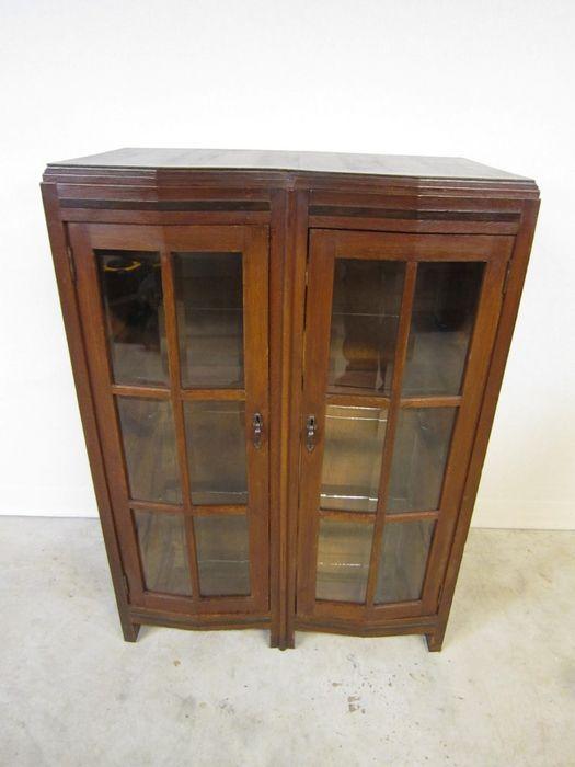 """Art Deco eikenhouten 2 deurs vitrine kastje met palissander """"lijsten"""". De glas en spiegelplaten van de kast zijn uit een latere tijd evenals de verlichting bovenin. Deze verlichting is heel simpel te verwijderen indien ongewenst. De glasdeuren bevatten een roedeverdeling met facetgeslepen glas. Er zijn geen sleutels bij maar indien gewenst worden deze bijgemaakt voor 20,- euro per stuk. De kast is stevig en verkeerd in een redelijk tot goede staat.   Afmetingen: ca. 80 cm breed, 47 ..."""