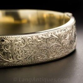 Lightly but sturdily crafted in 9ct. yellow gold in Chester, England - circa 1955 (according to the hall marks), the top half of this 1/2 inch wide hinged bangle bracelet is intricately and artfully hand-engraved with a charming floral design. A timeless, very wearable classic.