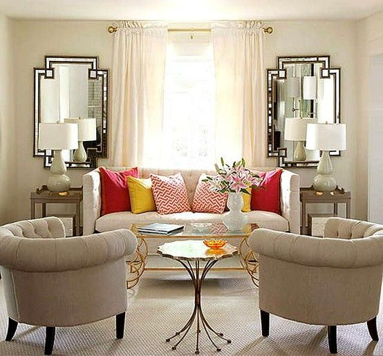 Ya gotta love the mirrors and the bright throw pillows in this small and neutral room.