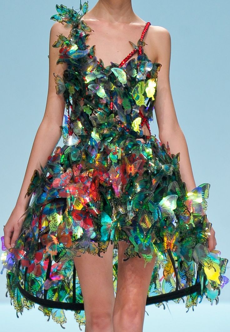This dress reminds of an enchanting forest, three dimensional decorative attachments deliver a vibrant feeling. Its unbalanced hemline, shorter in front and longer in the back, forms an oval-like shape or an open sphere. This gives an effect where the model is surrounded by a jungle-like atmosphere. The streak of red butterflies stand out among the rest of the greenish butterflies, a lovely vision.