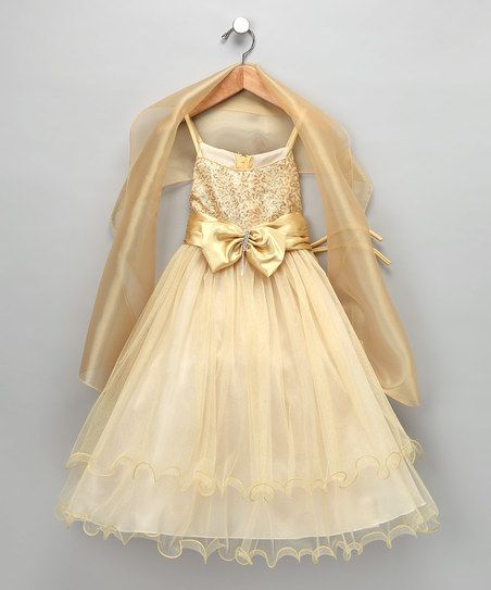 Something in the bottom of the skirt. That little curling edge...  Gold Bow Dress & Shawl - Toddler & Girls
