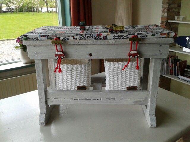 Speelbankje, met eigen gemaakte knoopjes van bamboe en leren veter. Kussentje er op met print van treinspoortjes, zodat er op de knietjes gespeeld kan worden! Je kunt er natuurlijk ook nog op zitten. In mandjes passen de autootjes.