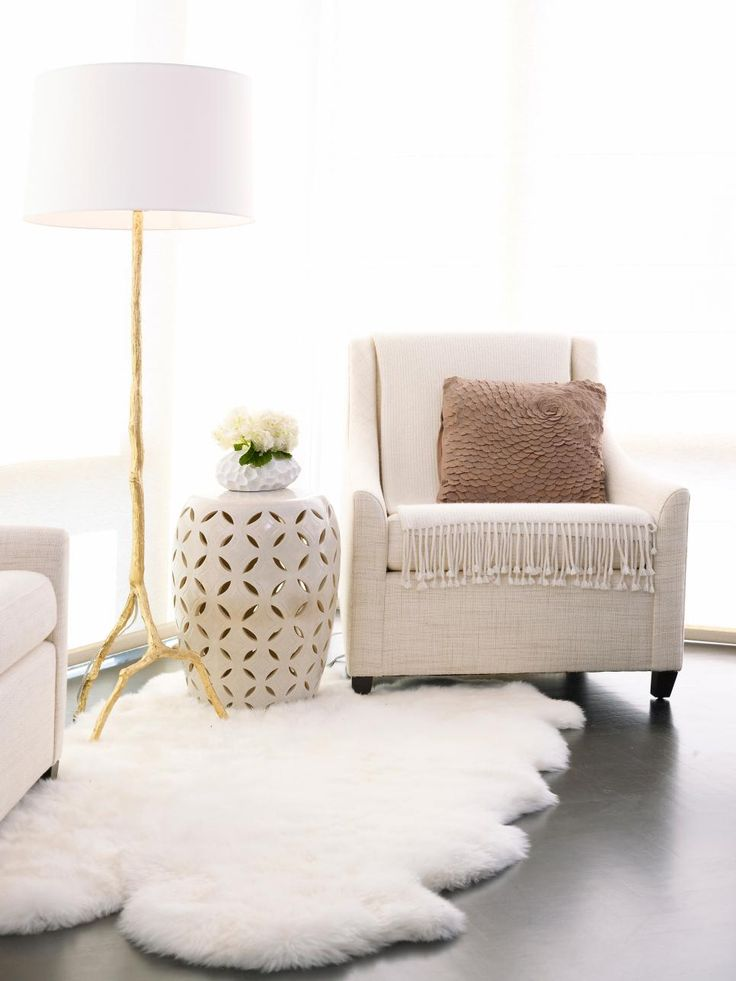 Neutral Upholstered Armchair With White Faux Fur Rug ll This chic sitting area features a neutral upholstered armchair with a taupe ruffled pillow and soft ivory throw. A natural tree branch floor lamp sits to the right of the armchair, while an ivory drum end table sits atop a white faux fur rug. #Interiors #Decor #White fairylights.com