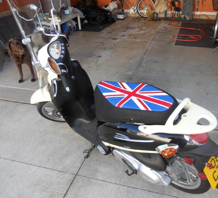 Kymco People 150 Scooter Seat Cover.  We love dogs, so any photo with a scooter AND a dog is guaranteed a spot on our website.  Scott wanted to give his white scooter a blast of color and went with this Union Jack seat cover with check denier sides. #CheekySeats