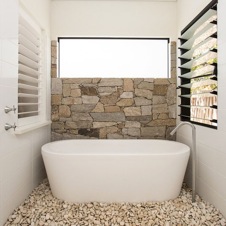 ensuite with stone wall feature and freestanding bath with pebble detail (SD Interiors)