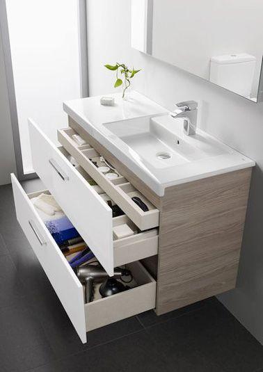 Dans une petite salle de bain, un meuble vasque en céramique blanche avec rangements intégrés, c'est une bonne idée pour gagner de la place. Petit tiroir discret et grands tiroirs s'associent pour offrir un espace futé sous le lavabo afin d'accueillir petits objets et serviettes de toilette. Un effet bi matière mixant finitions texturées en frêne clair et façades laquées blanc glossy avec barre de serviette latérale chromée pour un rangement salle de bain pratique qui a du style.